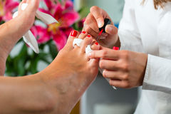 Woman in nail studio receiving pedicure Stock Photo