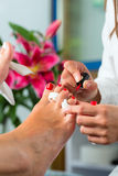 Woman in nail studio receiving pedicure Royalty Free Stock Images