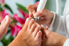 Woman in nail studio receiving pedicure Stock Image