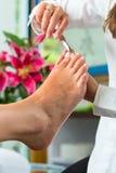 Woman in nail studio receiving pedicure stock photos