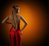 Woman Naked Back, Womanly Fashion Model Posing Sexy Red Dress. Elegant Girl Rear View Looking Side over Shoulder Stock Photography