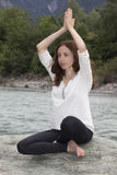 Woman in Namaste pose outdoors by a river royalty free stock photography