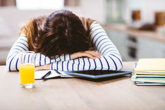 Woman napping with head by digital tablet and books. Close-up of woman napping with head by digital tablet and books on table Royalty Free Stock Photos