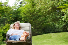 Woman napping outside. Mature woman dozing in a garden chair Royalty Free Stock Photos