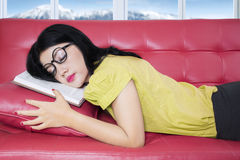 Woman napping on sofa after reading book Stock Photography