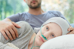 Woman with nasal cannula lying. Woman with oxygen nasal cannula and headscarf lying on couch Stock Photography
