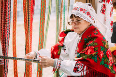 Woman in national Belarusian folk costume weaving belt. Belarus Stock Photography