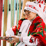Woman in national Belarusian folk costume weaving Stock Images