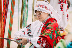 Woman in national Belarusian folk costume weaving Stock Photography