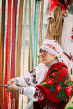 Woman in national Belarusian folk costume weaving Royalty Free Stock Images