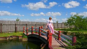 Woman in national dress goes with a basket on the bridge across the pond. stock footage