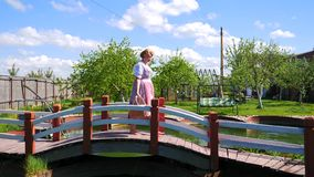 A woman in a national dress is walking along the beautiful bridge barefoot. stock footage