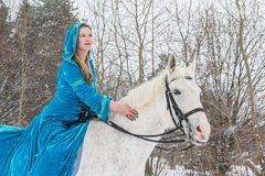 Woman in national dress and white horse in a winter forest Royalty Free Stock Image