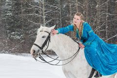 Woman in national dress and white horse in a winter forest Royalty Free Stock Photos