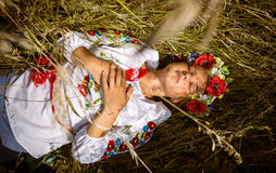 Woman in national ukrainian clothes with closed eyes lying on fi Royalty Free Stock Photo