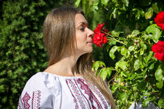 Woman in national ukrainian clothes smelling big rose at park Royalty Free Stock Photo