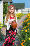 Woman in national ukrainian traditional costume holding a clay jug and welcoming guests Royalty Free Stock Photography