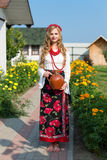 Woman in national ukrainian traditional costume holding a clay jug and welcoming guests Stock Image