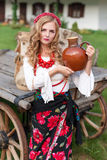 Woman in national ukrainian traditional costume holding a clay jug and welcoming guests Stock Photo