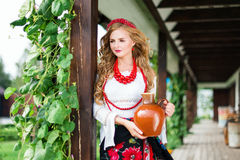 Woman in national ukrainian traditional costume holding a clay jug and welcoming guests Stock Photography
