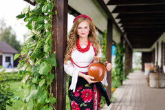 Woman in national ukrainian traditional costume holding a clay jug and welcoming guests Royalty Free Stock Photos