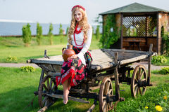 Woman in national ukrainian traditional costume holding a clay jug and welcoming guests Royalty Free Stock Images