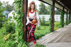 Woman in national ukrainian traditional costume holding a clay jug and welcoming guests Stock Photos