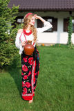Woman in national ukrainian traditional costume holding a clay jug and welcoming guests Royalty Free Stock Image