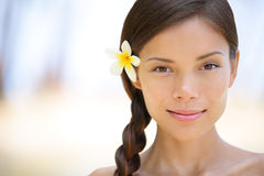 Woman natural beauty. Portrait of a beautiful and smiling brunette smiling outdoors with a flower in her braided hair. Multicultural Asian / Caucasian girl on Royalty Free Stock Photography