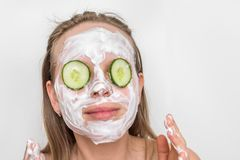 Woman with natural cream mask and cucumbers on her face. Funny woman with natural cream mask and cucumbers on her face - spa and beauty concept royalty free stock images