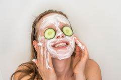 Woman with natural cream mask and cucumbers on her face. Funny woman with natural cream mask and cucumbers on her face - spa and beauty concept stock photography