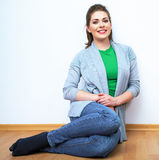Woman natural portrait. Smiling girl seat on a floor. White bac Royalty Free Stock Photos