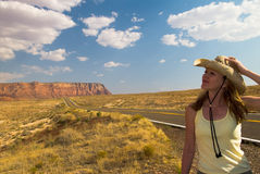 Woman in nature. Attractive blond caucasian woman wearing tank top and straw cowboy hat standing near a deserted highway with mountains and sky in the background Stock Photo