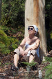 Woman in nature. Mature woman enjoying nature and taking a rest against a tree during a summer forest hike Royalty Free Stock Images