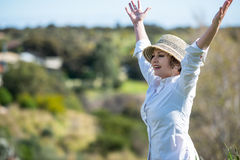 Woman in nature with arms outstretched Stock Photography