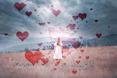 Woman in nature with artistic hearts stock photography