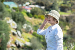 Woman in nature looking far. Woman with hat enjoying in nature and looking far royalty free stock photo