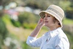 Woman  in nature looking far. Woman with hat enjoying in nature and looking far Stock Photo