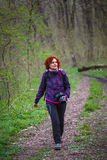 Woman nature photographer. Nature photographer with professional camera and backpack on a trail Stock Image