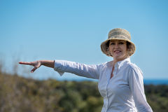 Woman in nature pointing away. Woman in hat  pointing away in nature Stock Photography