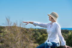 Woman in nature pointing away. Woman in hat sitting on the edge and pointing away Royalty Free Stock Photo