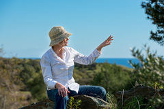Woman in nature pointing away. Woman in hat sitting on the stone and pointing away Royalty Free Stock Photos