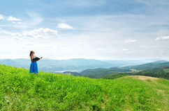 Red haired woman with book on the hilltop Stock Photography
