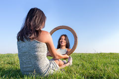 Woman in nature viewing her mirror image. Woman sitting on grass looking at  her mirror image Stock Images