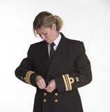 Woman navy officer buttoning her uniform jacket Stock Images