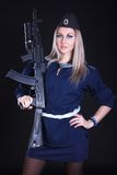 Woman in a navy uniform with an assault rifle Stock Image
