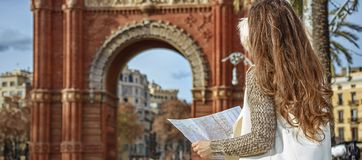 Woman near Arc de Triomf in Barcelona, Spain looking at map. In Barcelona for a perfect winter. Seen from behind elegant woman in earmuffs near Arc de Triomf in Royalty Free Stock Photos