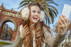 Woman near Arc de Triomf taking selfie with smartphone Royalty Free Stock Images