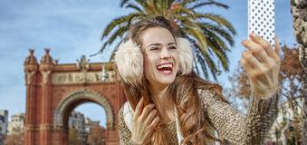 Woman near Arc de Triomf taking selfie with smartphone Royalty Free Stock Photos