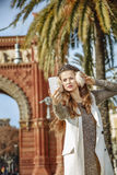 Woman near Arc de Triomf taking selfie with smartphone Stock Photo